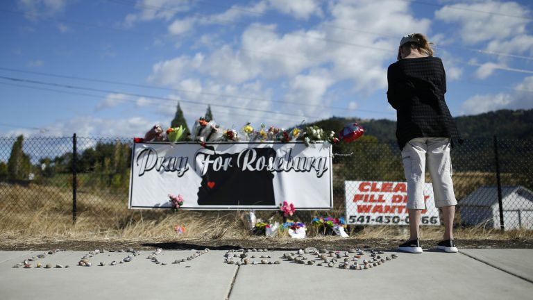A woman visits a makeshift memorial near the road leading to Umpqua Community College Saturday, Oct. 3, 2015, in Roseburg, Ore. Armed with multiple guns, Chris Harper Mercer, 26, walked in a classroom at the community college, Thursday, and opened fire, killing several and wounding several others. (AP Photo/John Locher)