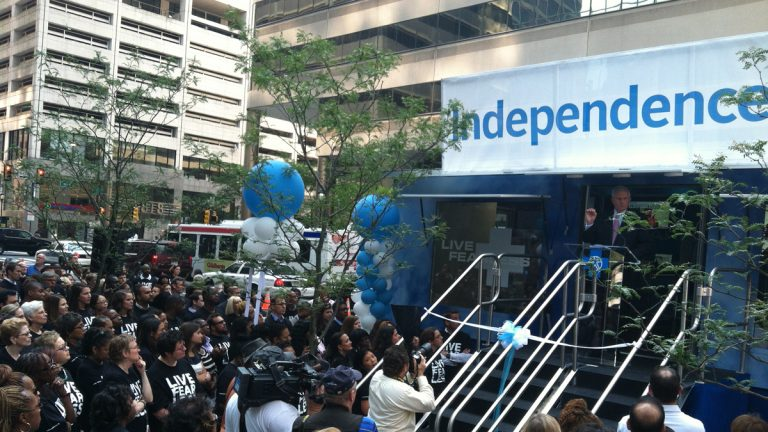 Employees and executives of Independence Blue Cross crowd around a new outreach truck parked outside the company's headquarters. (Elana Gordon/WHYY)