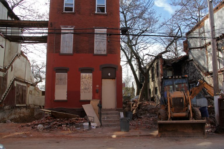 A home is demolished in the Sharswood section of North Philadelphia. (Emma Lee/WHYY)