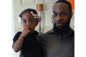Tyree Carroll holds his daughter (Carroll family photo)