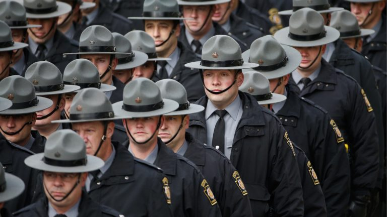 Officers salute as a hearse carrying the body of Jersey City Police Department Officer Melvin Santiago during a procession prior to funeral services. Santiago was shot in the head while still in his police vehicle July 13. His death has prompted some New Jersey lawmakers to call for reinstatement of the death penalty for police killers. (Julio Cortez/AP Photo)