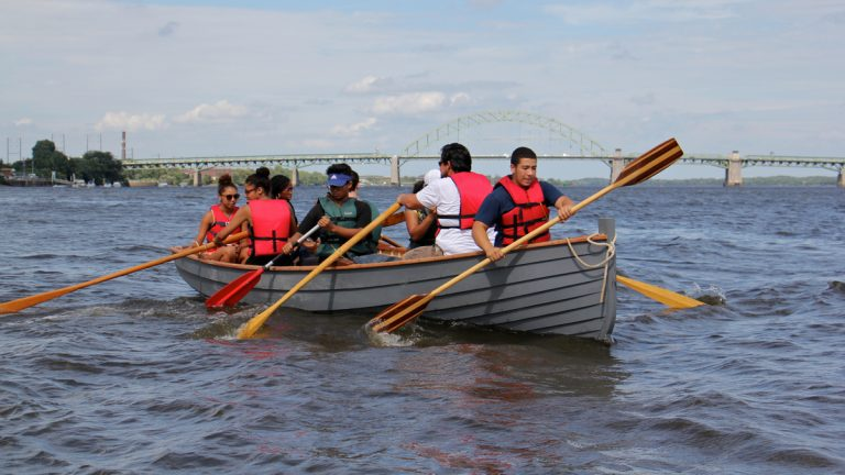 WorkReady students paddle on the Delaware River in a boat they built as part of the Wooden Boat Factory summer youth employment program. (Emma Lee/WHYY)