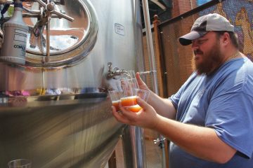 Evan Fritz, head brewer at Manayunk Brewing Company, draws off some samples of Papal Pleasure, a beer concocted to mark Pope Francis' visit to Philadelphia. (Emma Lee/WHYY