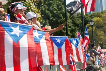 Specators hold Puerto Rican flags on the Ben Franklin Parkway during the 2014 Puerto Rican Day Parade in Philadelphia. (Brad Larrison/for NewsWorks)