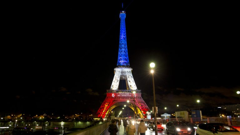 People walk towards the illuminated Eiffel Tower in the French national colors of red