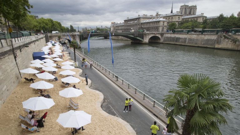 Tourists and Parisians take advantage of Paris Plage, an artificial beach set up on the right bank of the Seine river with palm trees, outdoor showers and hammocks in Paris, France, Monday, July 20, 2015.  (AP Photo/Michel Euler)