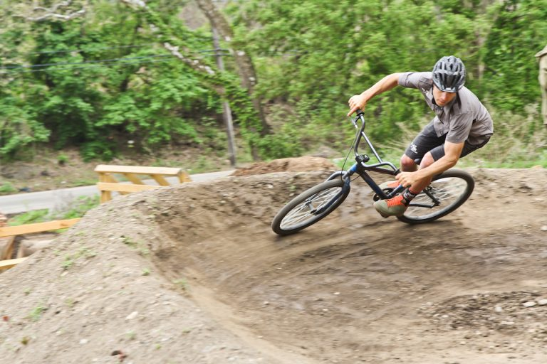 Professional cyclist and co-founder of Philly's first pump track Harlan Price demonstrates how to build momentum on the small track at the Parkside Evans Playground. (Kimberly Paynter/WHYY)