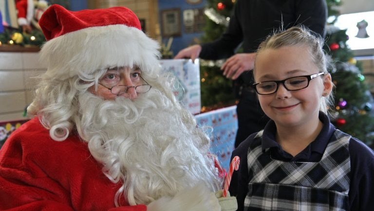 Riley Fitzpatrick asks Santa for a puppy at the 5th District Police Station Annual Christmas party. (Kimberly Paynter/WHYY)