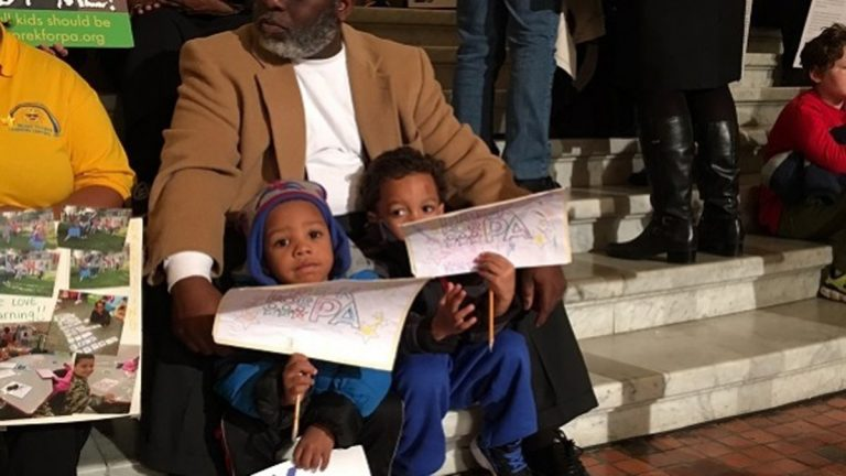 Pastor Scott Barkley, with the Bright Futures Learning Center in Harrisburg, sits with two of its 3-year-old students, Justice and Cortez, at the state Capitol. (Mary Wilson/WITF)