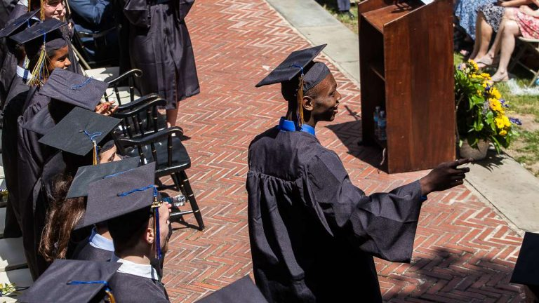 A graduate points to cheering audience members on his way to accept his diploma during Penn Charter's 2014 graduation ceremony. (Brad Larrison/for NewsWorks)