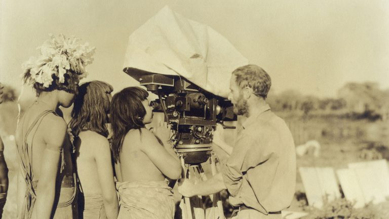 Academy Award-winning cinematographer Floyd Crosby, father of musician David Crosby, shows the expedition's experimental sound/film camera to the Bororo while filming