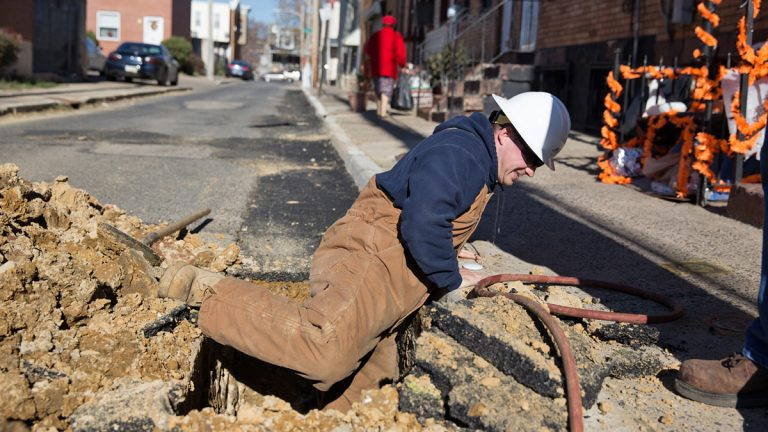 Michael Groves, PGW Senior Pipe Mechanic climbs out of a hole on Van Pelt Street after inspecting a new main gas line in North Philadelphia.  (Lindsay Lazarski/WHYY)