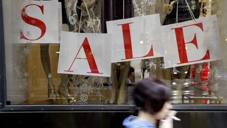 A person passes a retail store with sale sign displayed in the window in Philadelphia. (AP Photo/Matt Rourke, file)
