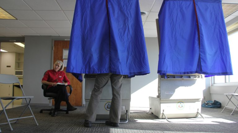 A voter in Philadelphia's 5th District casts her ballot in the solarium at Hopkinson House. (Emma Lee/WHYY)