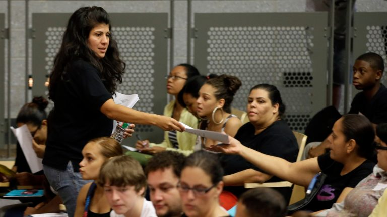 In this Aug. 29, 2013 photo, principal Debora Borges-Carrera hands out information packets to students and parents during an open house for incoming freshman and transfer students at Kensington High School for the Creative and Performing Arts in Philadelphia. (AP Photo/Matt Slocum)
