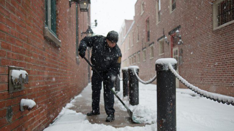 Wintry weather blankets the Philadelphia region. Firefighter Alberto Gonzalez shovels the sidewalk outside of the Fireman's Hall Museum in Old City. (Lindsay Lazarski/WHYY)