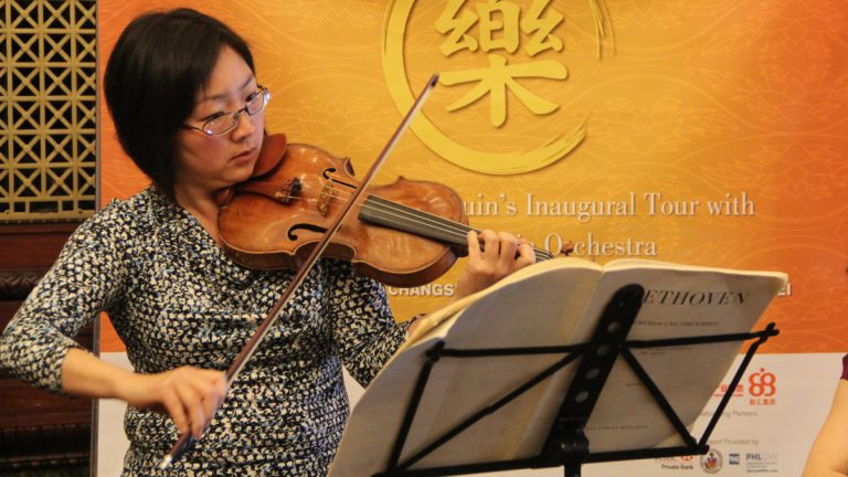 Philadelphia Orchestra's Juliette Kang plays at a press conference at City Hall to announce the orchestra's tour of China. (Emma Lee/WHYY)
