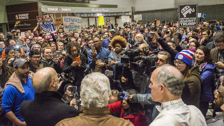 Media and protesters crowd around, (from left), Governor Tom Wolf, Representative Bob Brady, and Senator Bob Casey as they speak about their opposition and the developing situation regarding President Donald Trump's executive order on immigration at the Philadelphia International Airport. (Branden Eastwood for NewsWorks)