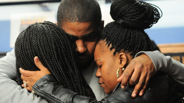 Carlesha Freeland-Gaither's family consoling one another at a press conference on Tuesday afternoon. Her mother, Keisha, is on the right. (Bas Slabbers/for NewsWorks)