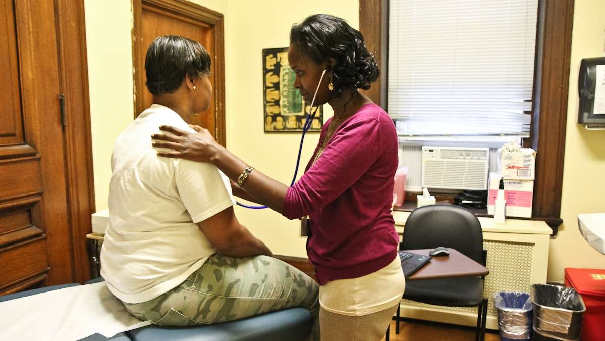 Lucy Kibe examines patient Sherri Robinson at St. Elizabeth Wellness Center