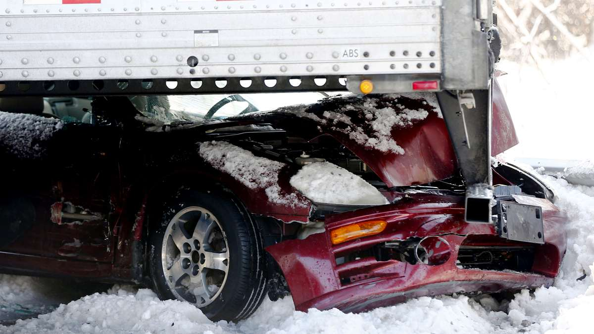 A car is wedged under a semi-trailer in a huge pile-up on the Pennsylvania Turnpike in Bensalem, Pa. (Matt Rourke/AP Photo)