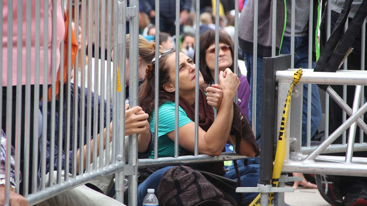 A woman clings to the bars of a barricade as she watches Pope Francis on a jumbotron near City Hall. (Emma Lee/WHYY)