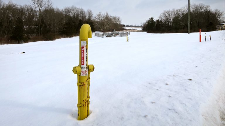A marker shows the path of the Texas Eastern Pipeline as it runs under a field in Lambertville, New Jersey. It is one of several natural gas pipelines buried under farms, forests, backyards and waterways in the region. (Katie Colaneri/WHYY)