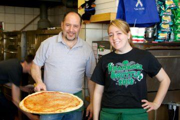Nunzio Esimeo shows off a fresh cheese pizza, with Danielle Lagomarisno at Montesini Pizza (Nathaniel Hamilton/for NewsWorks)