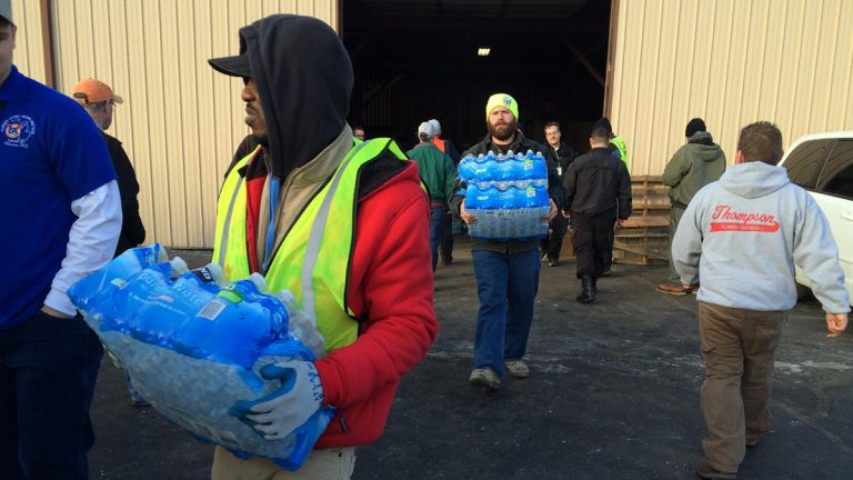 Volunteers load water into plumbers' vans and trucks.