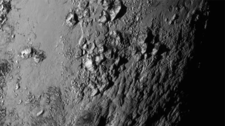 This image provided by NASA on Wednesday shows a region near Pluto's equator with a range of mountains captured by the New Horizons spacecraft. (NASA/JHUAPL/SwRI via AP)