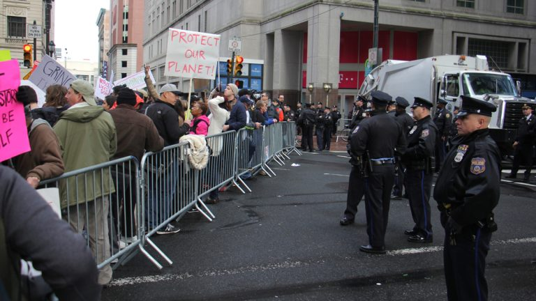 Police stand guard behind barricades keeping protesters well away from the entrance to the Loews Hotel