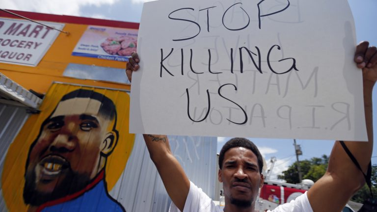 A man holds a sign in front of a mural of Alton Sterling while attorneys