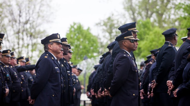 Philadelphia Police Officers stand at the Living Flame Memorial for fallen officers and fire fighthers in Franklin Square