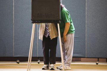Voting machine operator George Stuski reads a newspaper as people cast their votes at the Mummer Museum in Philadelphia, Pa.  (AP Photo/ Joseph Kaczmarek)