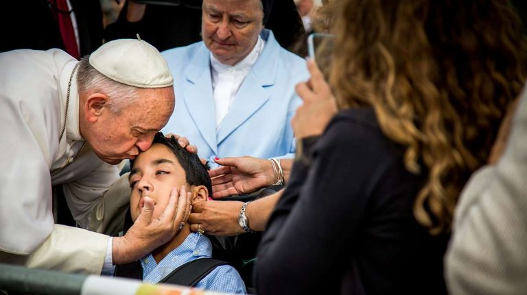 In this photo provided by World Meeting of Families, Pope Francis kisses and blesses Michael Keating, 10, of Elverson, Chester County,  after arriving in Philadelphia and exiting his car when he saw the boy Sept. 26. Michael has cerebral palsy and is the son of Chuck Keating, director of the Bishop Shanahan High School band that performed at Pope Francis' airport arrival. (Joseph Gidjunis/World Meeting of Families via AP)