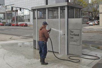 Rodney Haven, of Clean and Safe, washes down the exterior of a Portland Loo in Portland, Ore. The city installed solar-powered, stainless steel public toilets that its workers developed and dubbed the Portland Loo.  (AP Photo/Rick Bowmer, File)