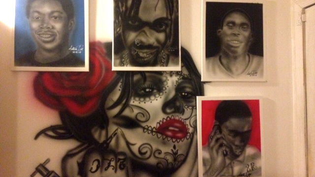 Tattoo artist Aaron 'Black Picasso' Ray paints portraits of some Wilmington homicide victims, giving them to families hoping to help them heal. (Anne Hoffman/for NewsWorks)