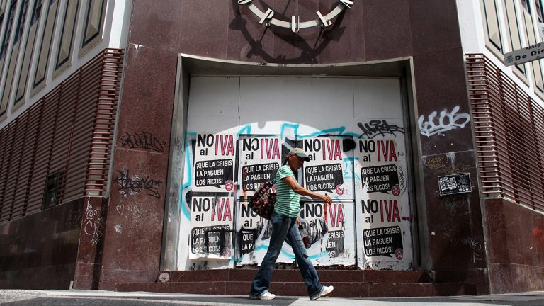 A woman walks in front of a closed down bank in the neighborhood of Rio Piedras in San Juan