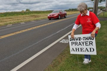 Ruth Portzline is the Pastor of Saint John's United Methodist church in Ivyland, Pa. She stakes a sign inviting motorists to pray with volunteers a few plots down from the church. (Kimberly Paynter/WHYY)