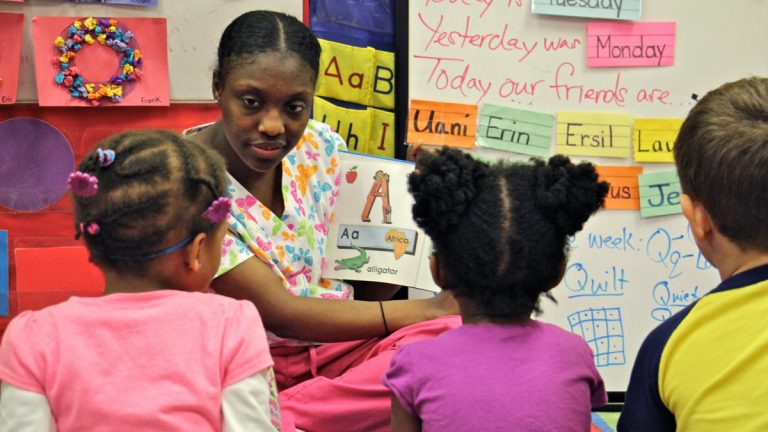 Pre-K teacher Shirell Peaker reads with children at Little Learners Literacy Academy in South Philadelphia. (Emma Lee/WHYY)