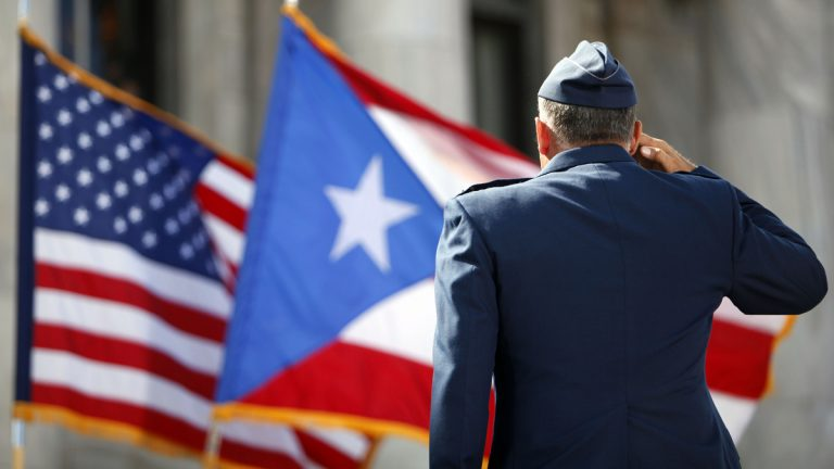 A U.S. Army honor guardsman salutes the Puerto Rican and U.S. flags during the inaugural ceremony for governor-elect Alejandro Garcia Padilla, at the Capitol building in San Juan on Wednesday, Jan. 2, 2013. Puerto Ricans endorsed U.S. statehood for the Caribbean island — and in the same election ousted pro-statehood governor Luis Fortuno. (AP Photo/Ricardo Arduengo)