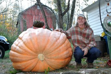 Alex McCracken shows off a giant pumpkin that mysteriously stopped growing early in the season at his Quakertown home. (Carolyn Beeler/WHYY)
