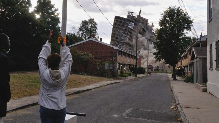 City Councilwoman Cindy Bass applauds after pushing the 'detonator' that sent the Queen Lane Apartment demolition in motion on Saturday. (Bas Slabbers/for NewsWorks)