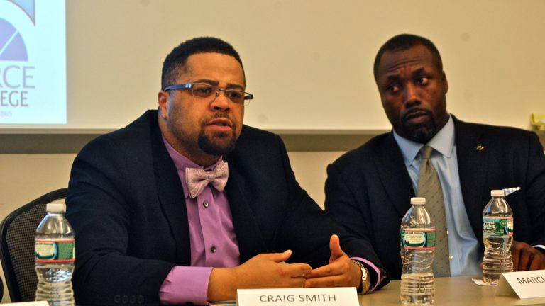 Panelist Craig Smith of Year Up Philadelphia speaks while Marcus Allen, CEO of Big Brothers/Big Sisters Southeastern Pennsylvania, listens during a discussion on race relations at Peirce College. (Sara Hoover/for NewsWorks)