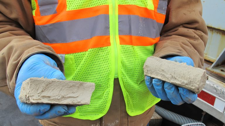 A worker breaks apart a brick of solid material left over from treating frack water. The solid material, which may contain radioactive elements, gets disposed of in landfills. (Susan Phillips/StateImpact Pennsylvania)