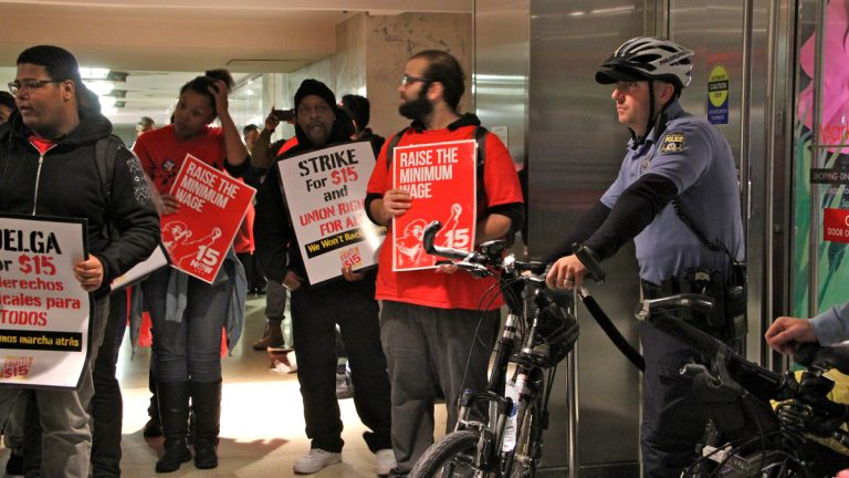 Philadelphia police block  demonstrators rallying for a minimum-wage hike from entering the food court at the Comcast building Tuesday. (Emma Lee/WHYY)