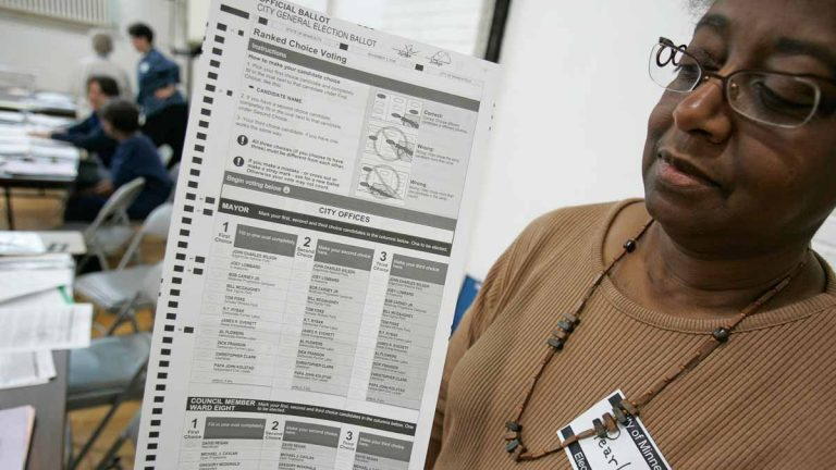 An election judge holds up a general election ballot featuring new ranked choice voting