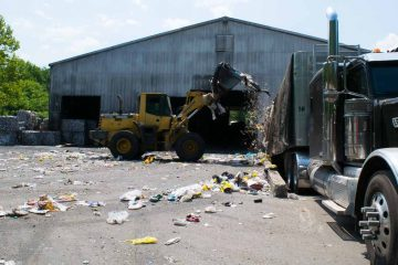 A front loader scoops up  trash that has accumulated at the Omni Recycling Plant in Pitman