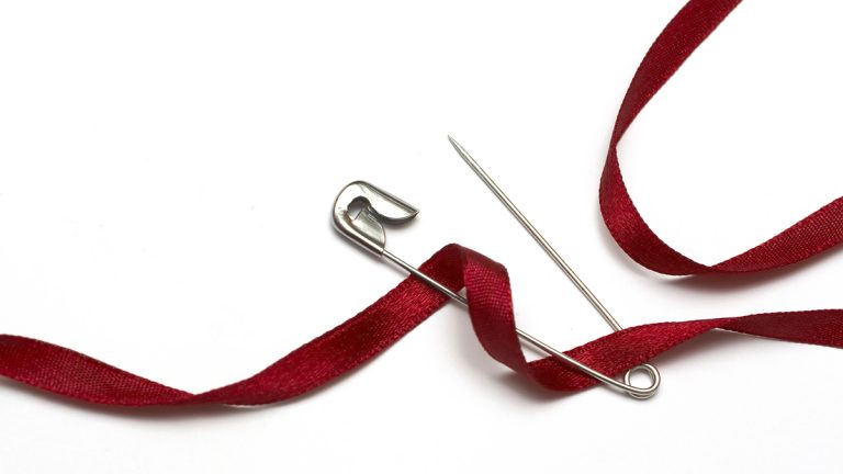 (<a href='http://www.bigstockphoto.com/image-26363870/stock-photo-safety-pin-and-red-ribbon'>pcatalin</a>/Big Stock Photo)
