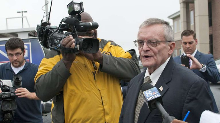 Reporters flank former Harrisburg Mayor Stephen Reed after his arrest on bribery, theft and corruption charges. (Diana Robinson/WITF)
